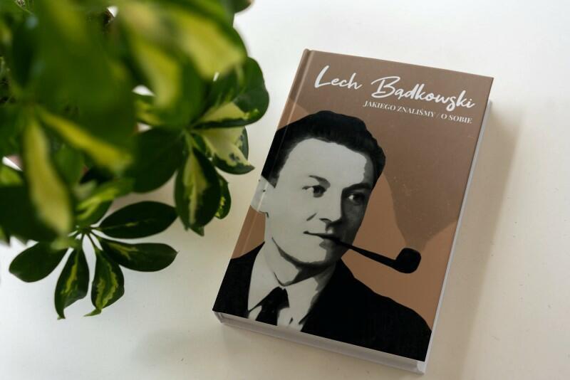 """Po prawej stronie na białym stole leży książka: """"Lech Bądkowski jakiego znaliśmy. Lech Bądkowski o sobie"""". Na okłądce czarno-biały portret mężczyzny. Po lewej stoi roślinka doniczkowa o dużych ,licznych zielonych liściach"""