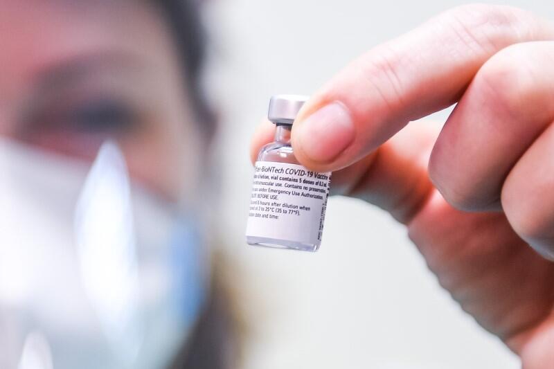 Na pierwszym planie widać fiolkę ze szczepionką. Trzyma ją w palcach gołej dłoni kobieta, która na twarzy ma białą maseczkę