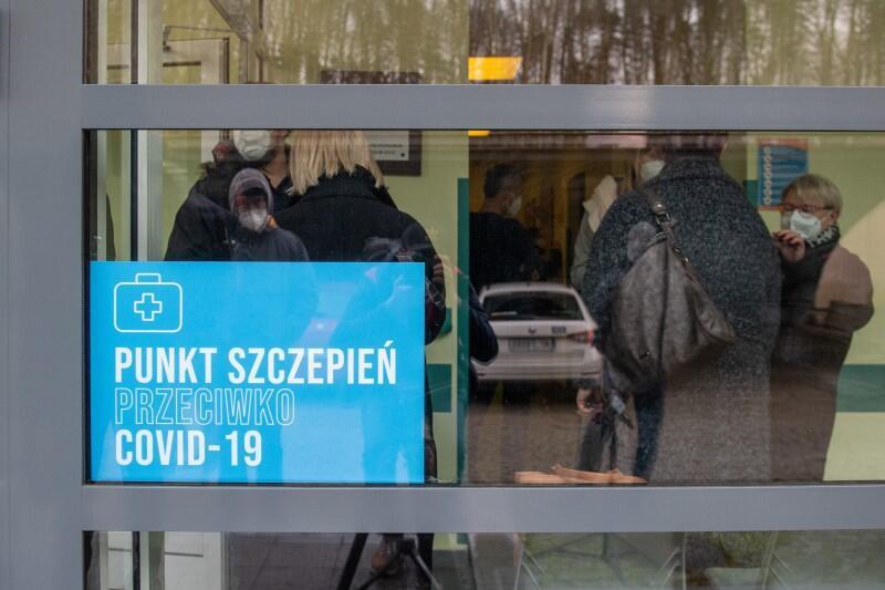 Przeszklone wejście do jednego ze szpitalnych oddziałów. Za szybą napis informujący, że tutaj znajduje się punkt szczepień przeciwko covid, widać też kilka osób w maseczkach