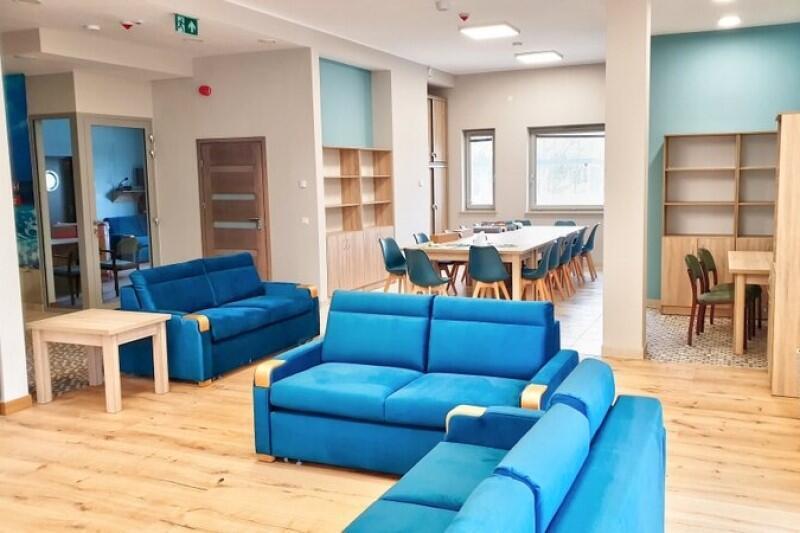 Jedno z pomieszczeń pogotowia opiekuńczego. Na pierwszym planie znajdują się niebieskie kanapy, w głębi pomieszczenia jest długi stół, wokół którego ustawiono kilkanaście krzeseł. Są też regały z półkami. Całość utrzymana w kremowo-niebieskiej tonacji kolorystycznej