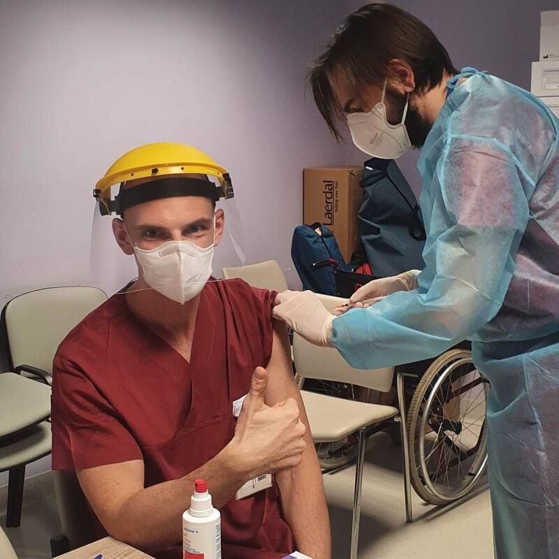 Mężczyzna w średnim wieku siedzi, młodszy mężczyna w stroju medycznym pochylony nad nim, w ręku trzyma strzykawkę