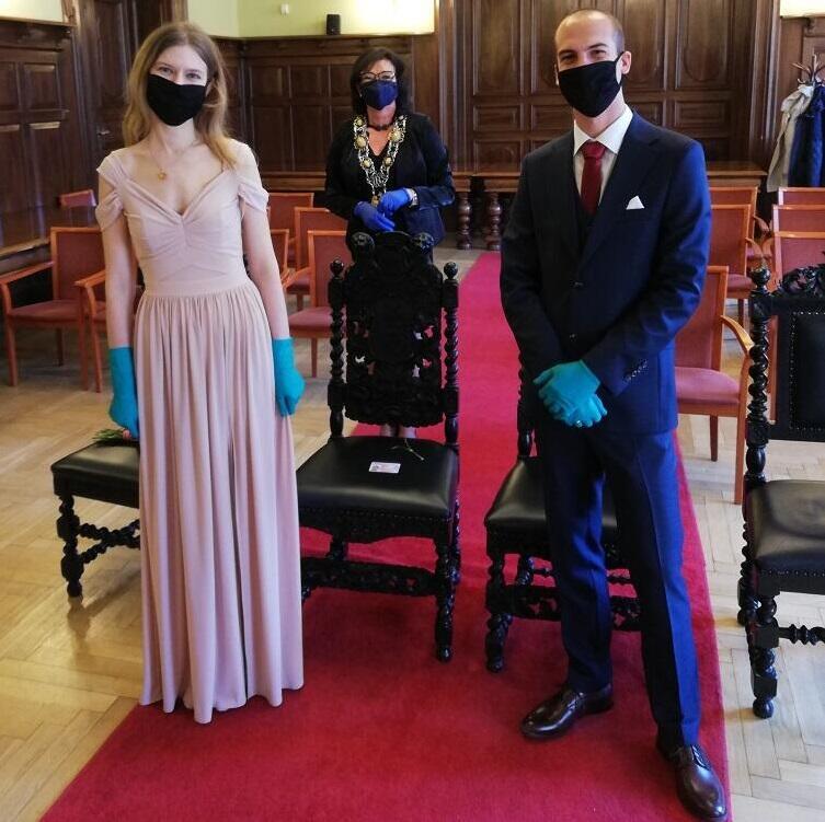 Pani Anna i pan Stefan małżeńską przygodę rozpoczęli 17 kwietnia, w pełni pierwszego lockdownu, dlatego mają jeszcze na dłoniach jednorazowe rękawiczki. Za nimi Grażyna Gorczyca kierownik Urzędu Stanu Cywilnego, która udzieliła im ślubu