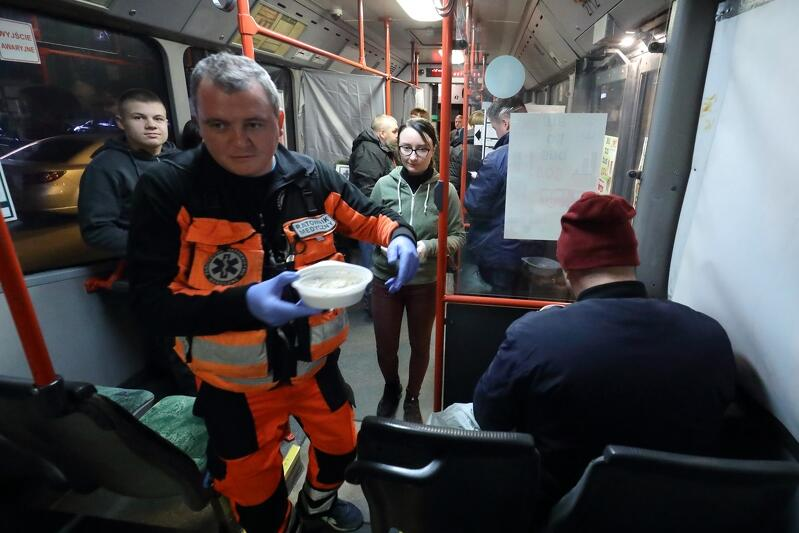 Wnętrze gdańskiego autobusu S.O.S. - na pierwszym planie ratownik medyczny z talerzem gorącej zupy, wokół kilka osób korzystających z pomocy