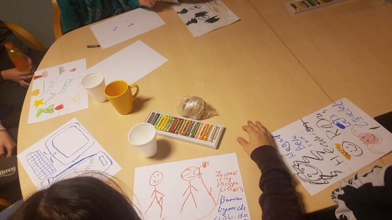 Stół, kartki papieru,rysunki na kartkach, ręce dzieci