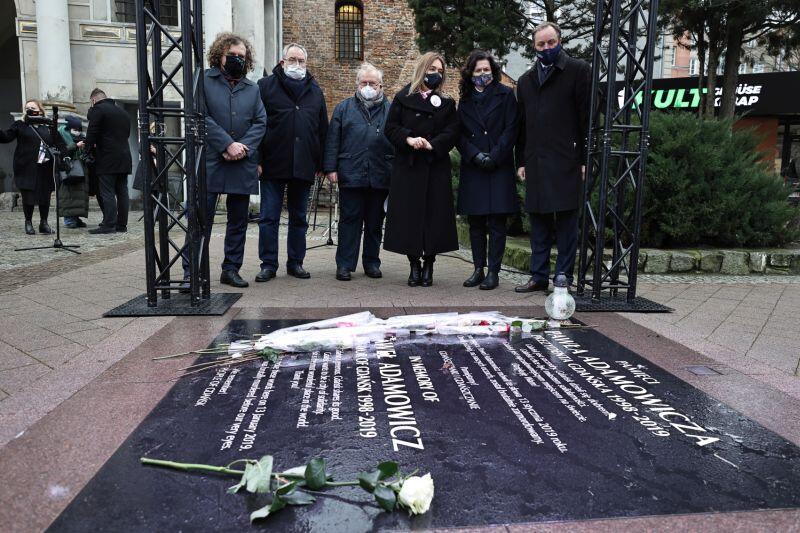 Uczestnicy konferencji przy tablicy upamiętniającej miejsce śmierci Pawła Adamowicza