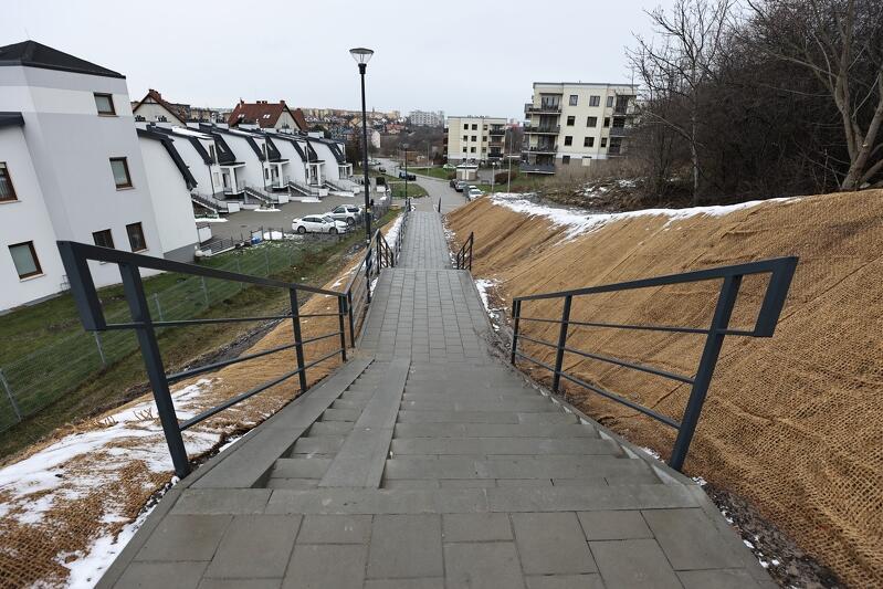 na zdjęciu widać fragment schodów, są w kolorze szarym, z obu ich stron zamontowano ciemne barierki. po lewej stronie fragment zabudowy wielorodzinnej, budynki są białe, mają granatowe dachy