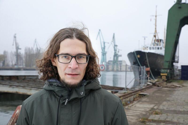 Na zdjęciu portretowym Ilia Pyzhin, młody mężczyzna, szatyn z bródką, nieco dłuższe niż za uszy włosy, okulary, patrzy w obiektyw. Za nim dźwigi stoczniowe. Ma na sobie ciemno-zieloną zimową kurtkę