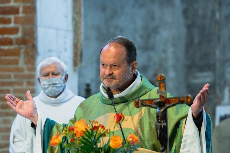 ksiądz w szatach liturgicznych w geście błogosławieństwa stoi przy ołtarzu, z księdze szafarz w białej szacie