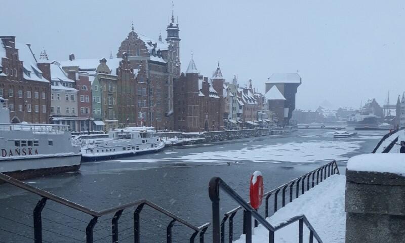 Motława na odcinku z widokiem na zabytkowy Żuraw Gdański. Rzeka częściowo przykryta warstwą bieli, ale chyba jeszcze nie lodu. Nabrzeże zaśnieżone, dachy domów też pokryte bielą