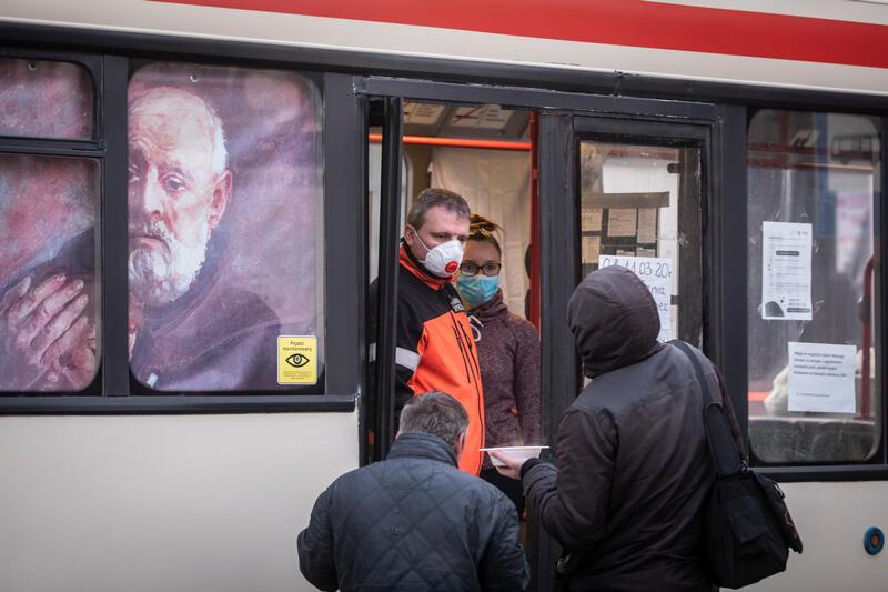 Fragment autobusu, na którym jest wizerunek brata Alberta. W srodku dwie osoby w maseczkach ochronnych, dwie osoby na zewnątrz odwrócone tyłem, jedna z nich trzyma w dłoni miskę