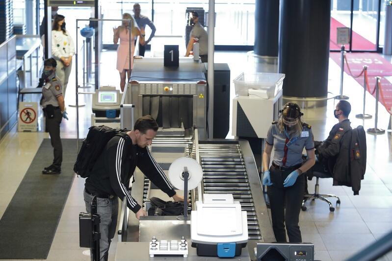 scena z odprawy na lotnisku, pracowniczka straży granicznej z twarzą zasłoniętą przyłbicą, pasażer z odkrytą twarzą, ludzie w tle