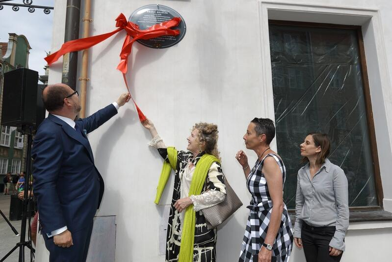 Prezydent Adamowicz stoi po lewej, na prawo od niego stoją kolejno trzy kobiety. Nad ich głowami, na ścianie budynku widać ciemnozieloną tablicę o owalnym kształcie, na której trzyma się jeszcze niezerwana czerwona wstęga