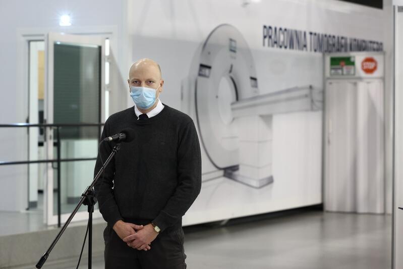 dr Piotr Kobzdej pełnomocnik wojewody pomorskiego ds. organizacji szpitali tymczasowych i ds. szczepień, za nim pracownia tomograficzna szpitala tymczasowego w AMBEREXPO