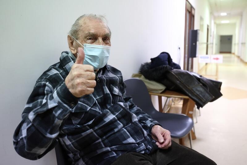 Starszy mężczyzna siedzi, unosi kciuk do góry