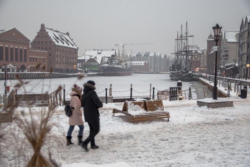 Widok ośnieżonego nabrzeża Motławy. Spacerują dwie osoby. Po prawej widać statek i znajdującą się za nim sylwetkę gdańskiego Żurawia
