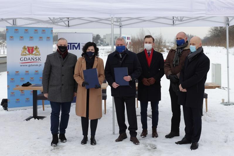grupa osób w zimowym plenerze z maseczkami, trzymają w dłoni teczki z dokumentami