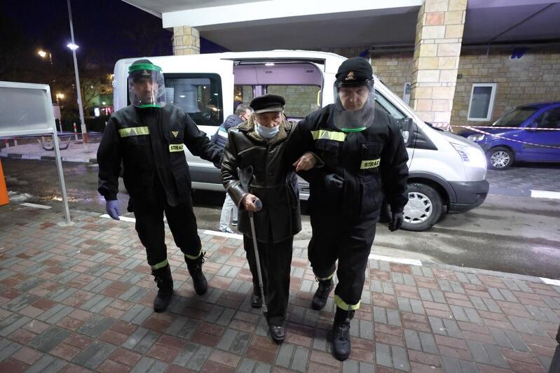 Trzech mężczyn, w środku starszy mężczyzna w zimowej kurtce, po bokak młodzi mężczyżni w mundurze z napisem straż