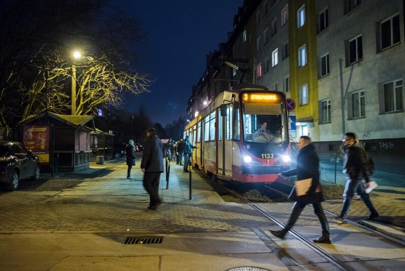 zdjęcie wykonane wieczorową porą, na pierwszym planie dwóch mężczyzn przechodzi przez tory tramwajowe, obok nich stoi oświetlony tramwaj w kolorach biało-czerwonym, po prawej stronie widac kilkupiętrowy szary budynek mieszkalny