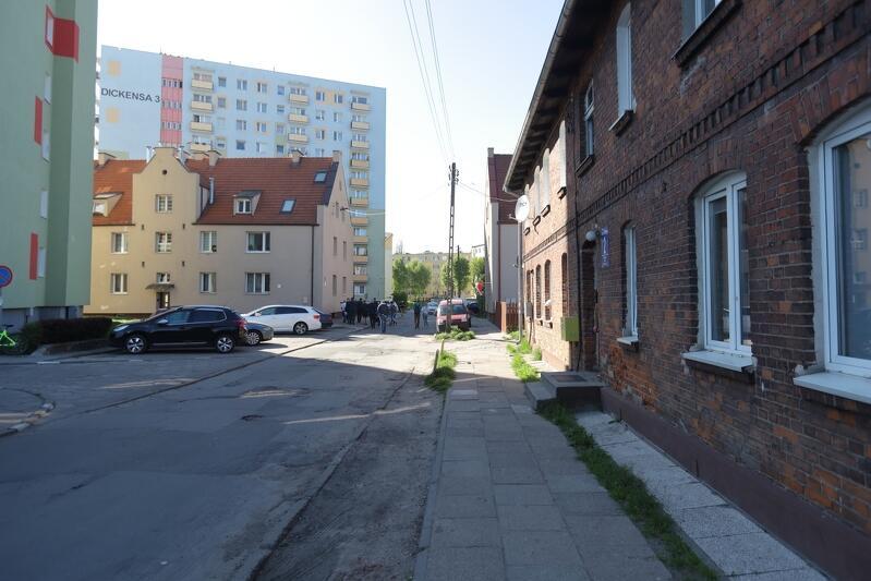 na pierwszym planie po prawej widać fragment starej kamienicy zbudowanej z cegły, w tle stoją wysokie bloki mieszkaniowe, widać też fragment jezdni i chodnika przy kamienicy