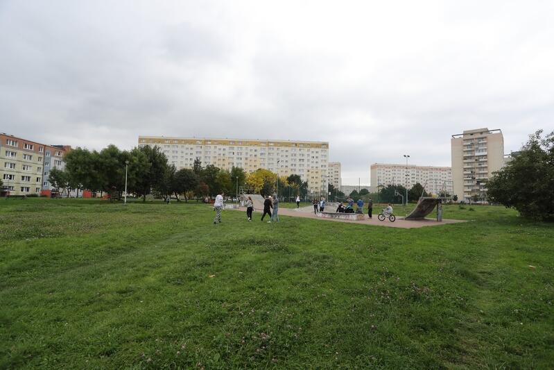 na pierwszym planie widać szeroki zielony pas trawnika, w tle betonowy plac z konstrukcjami do jazdy na deskorolce bądź specjalnych rowerach, na placu stoi kilkanaście osób, w tle stoją trzy kilkunastopiętrowe szerokie bloki mieszkaniowe.