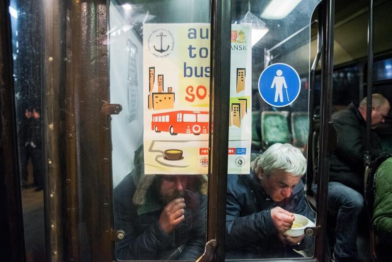 Autobus, w środku dwóch starszych meżczyzn je zupę