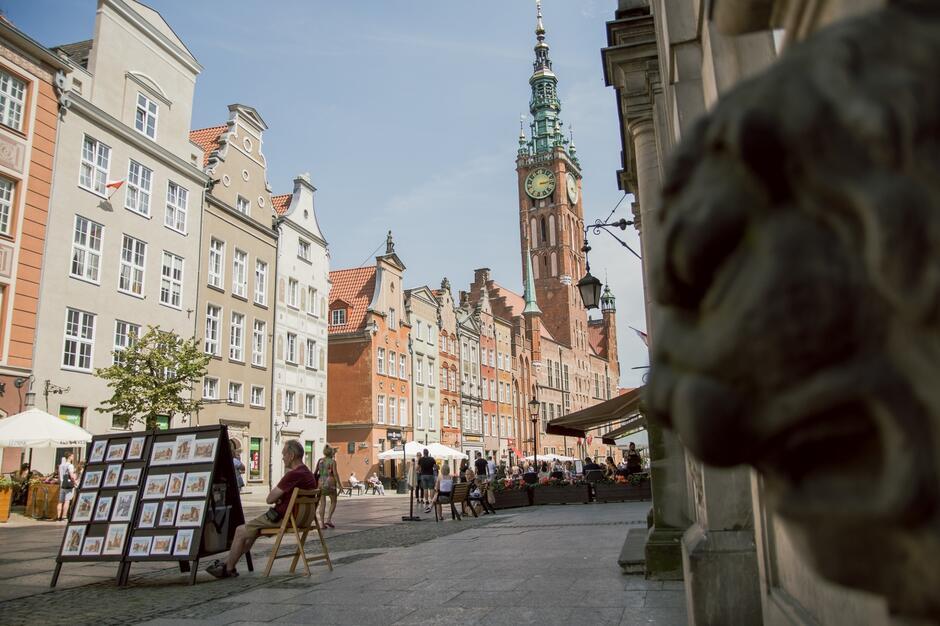 Zdjęcie przedstawia widok na ulicę Długą w gdańsku. Na skraju widoczne stoisko z pracami plastycznymi, które można zakupić.
