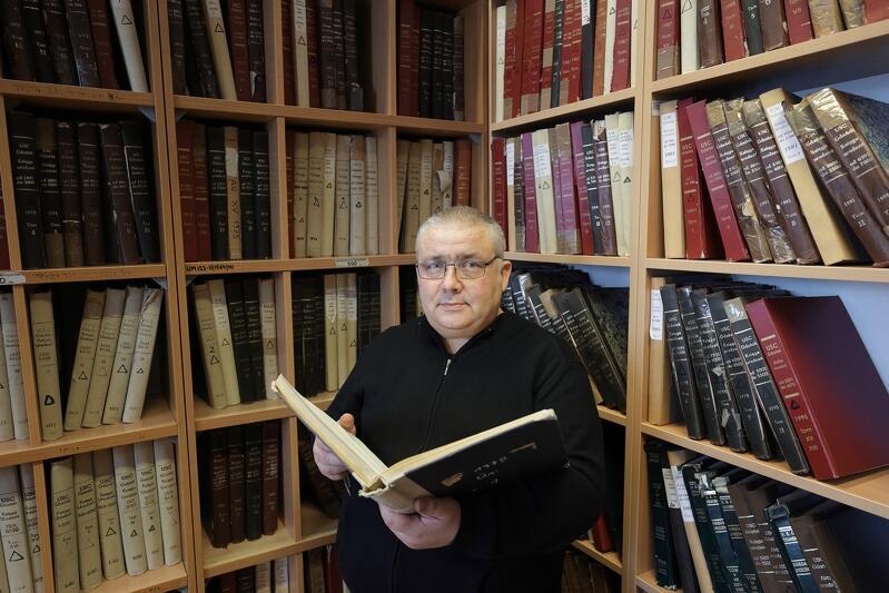 Inspektor Bogusław Mrowiński z zapałem bada dzieje swojego miejsca pracy - Urzędu Stanu Cywilnego w Gdańsku, w rękach - otwarta księga z archiwum USC