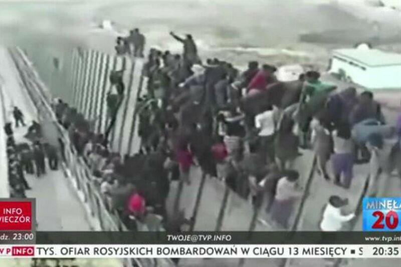 Kadr z filmu przedstawia tłum imigrantów forsujących mur na granicy jednego z państw europejskich