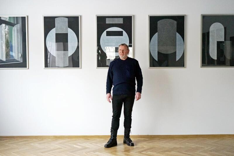 Stanisław Olesiejuk, artysta pozuje w galerii - białe ściany, jasne, drewniane podłogi - na tle swoich prac. Kilka czarno-białych rysunków wisi na ścianie. Artysta jest ubrany na czarno