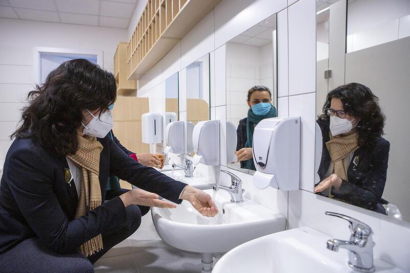 Kobieta w maseczce kuca przy umywalce i myje ręce, widać jej odbicie w lustrze. W drugim lustrze, widać odbicie drugiej kobiety