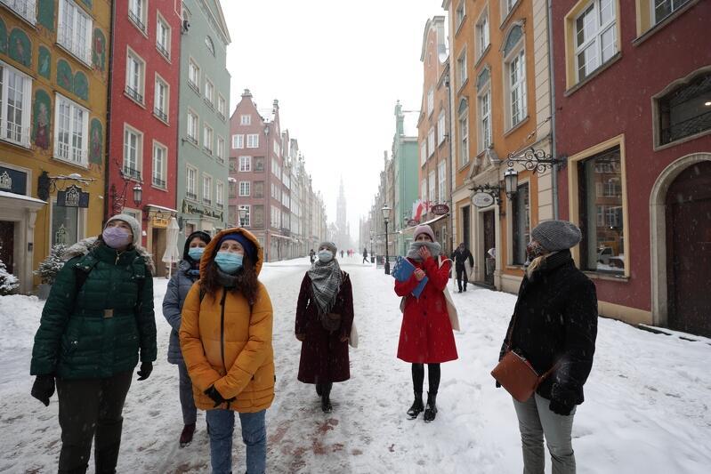 Ulica Długa w Gdańsku, stoi kilka osób, patrzy na kamieniczki