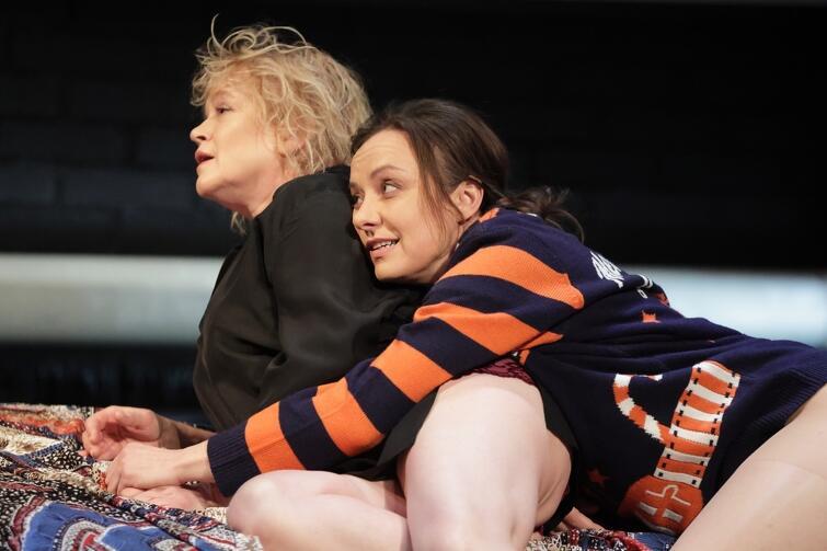 dwie kobiet leżą na łóżku, jedna z nich obejmuje drugą, patrzą w dal słuchając czegoś