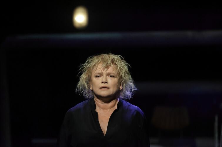 Portret kobiety ok. 50 letniej, ma do ramion blond włosy i czarną koszulę