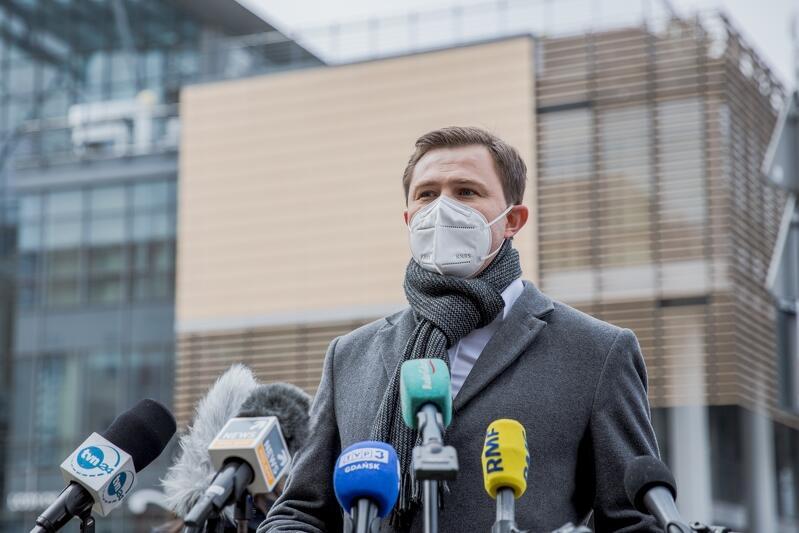 Piotr Grzelak zastępca prezydent Gdańska podczas konferencji prasowej, 2 marca 2021, w tle - oczyszczone z niezgodnych z Uchwałą Krajobrazową Gdańska - Centrum handlowe Manhattan