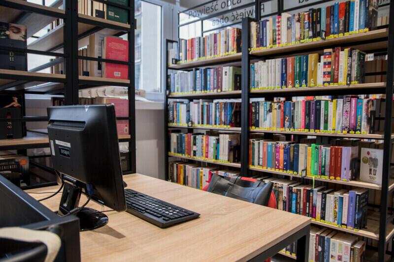 Wnętrze biblioteki, po lewej stronie biurko z płaskim czarnym ekranem komputera, w tle i po prawej stronie metalowo-drewniane regały z książkami