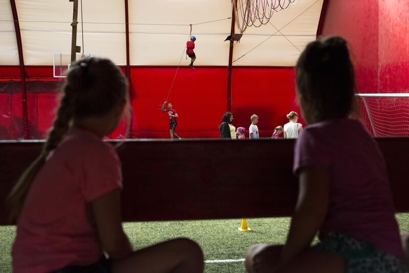 Dwi dziewczynki siedzą, przyglądają się scenie, na które inne dziecko wspina się na linie