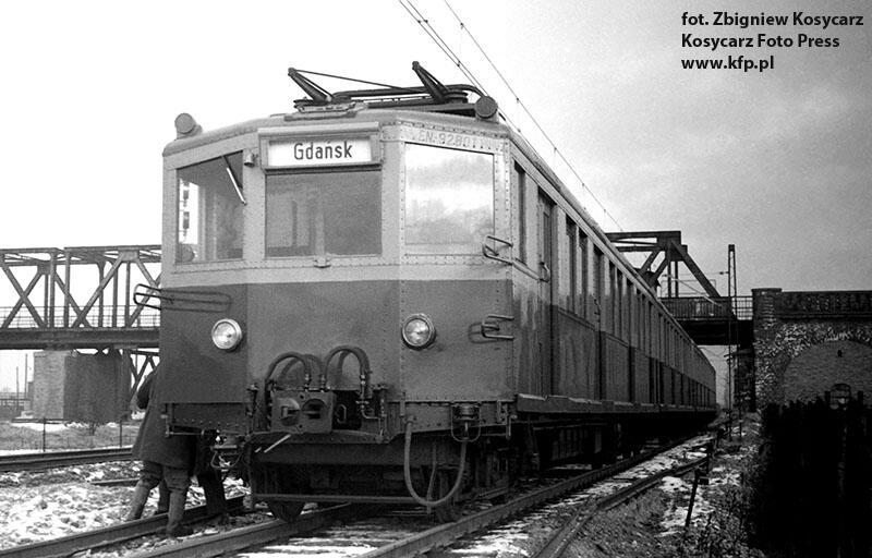 Lata 50-te XX w. Pociąg elektryczny popularny modrak  stoi obok wiaduktu na ul. Uczniowskiej w Gdańsku Letnicy