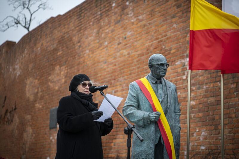 Krystyna Zachwatowicz-Wajda stoi obok pomnika, po jego lewej stronie, i czyta z kartki do mikrofonu przygotowany tekst krótkiego przemówienia