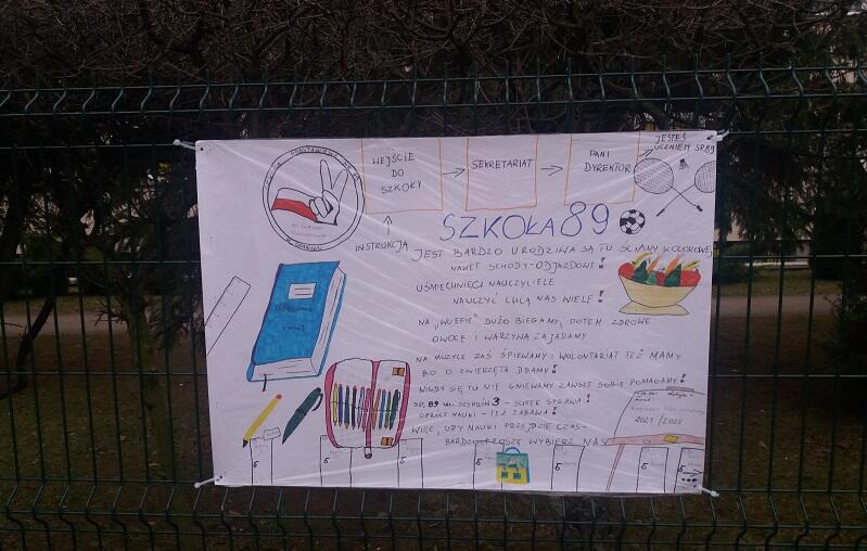 Jeden z plakatów zachęcających do wybrania Szkoły Podstawowej nr 89 w Gdańsku, wiszą na płocie placówki