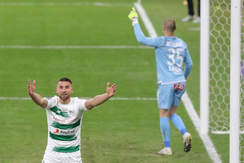 Łukasz Zwoliński w biało-zielonym stroju, na polu karnym Lecha Poznań. Gdański zawodnik przed chwilą strzelił gola, ale sędzia go nie uznał z powodu spalonego. Zwoliński stoi po lewej stronie zdjęcia, z rozpostartymi w górę rękami, ma zdziwiony wyraz twarzy - jakby chciał przekonać sędziego, że ten się myli. Po prawej stronie zdjęcia, przy bramce, stoi w jasnoniebieskim stroju bramkarz Lecha. Ten z kolei wyciąga w górę jedną rękę, by potwierdzić decyzję sędziego, że jednak był spalony