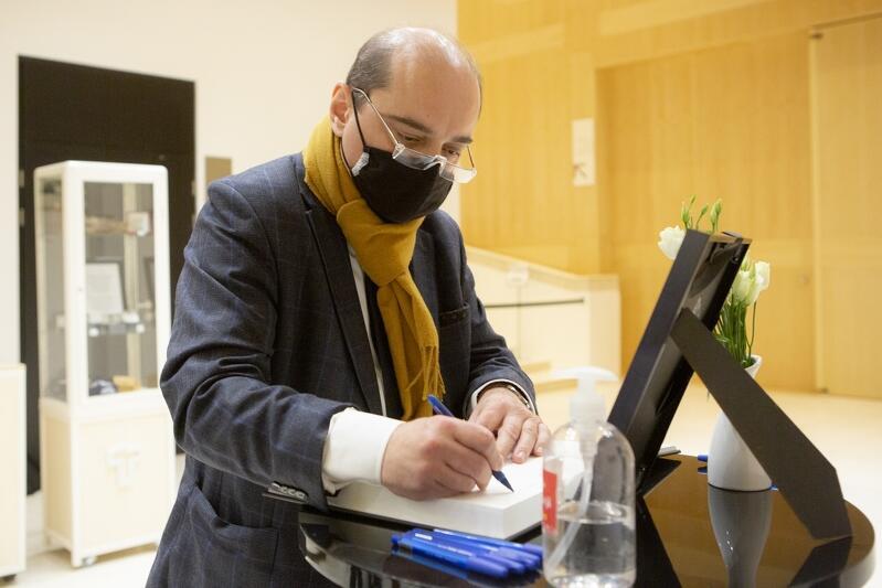 Mężczyzna w maseczce ochronnej pochyla się z długopisem nad stolikiem i otwartą księgą. Obok księgi stoi niewielkie zdjęcie portretowe Jerzego Limona i wazonik z białymi goździkami