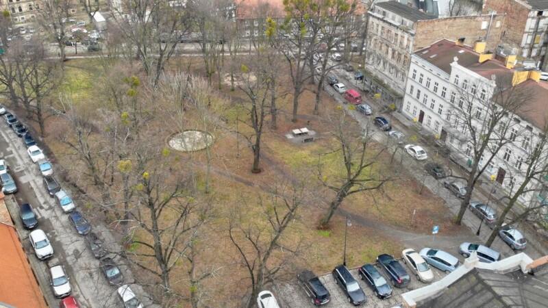 Zadrzewiony plac, otoczony budynkami. Zdjęcie wykonano z dachu najwyższego budynku. Plac jest dobrze widoczny, ponieważ jest przedwiośnie, drzewa nie mają jeszcze liści. Wzdłuż boków placu stoją gęsto zaparkowane samochody