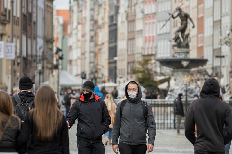 Ulica Długi Targ w Gdańsku, pomnik Neptuna, ludzie idący w maseczkach