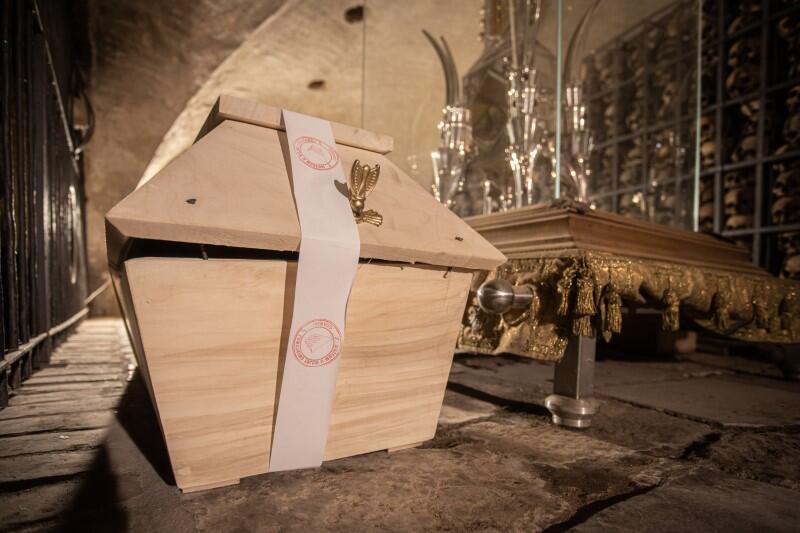 Trumna z jasnego drewna, stojąca w niskiej sali o łukowatym sklepieniu