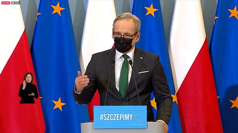 Mężczyzna w srednim wieku, w masecze, prze mikrofonem, w tle flagi Polski i UE