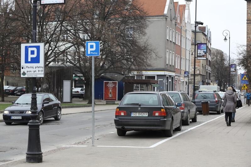 Widok ulicy w Śródmieściu Gdańska. Na miejscach parkingowych, przy poboczach chodników, zaparkowane są samochody - jeden za drugim