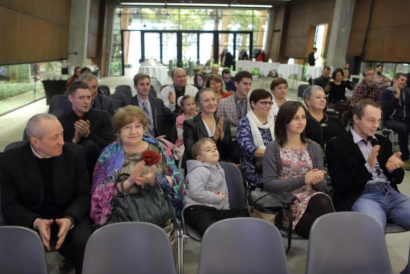Gruba dwudziestu osób w różnym wieku, które siedzą na krzesełkach w ECS. Część z nich bije brawo osobom, które znajdują się na scenie, ale zdjęcie ich nie pokazuje