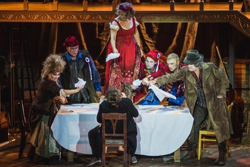 Siedmioro aktorów siedzi w kolorowych strojach przy stole, ustawionym na scenie. Jeden z aktorów siedzi na krześle, plecami do widowni