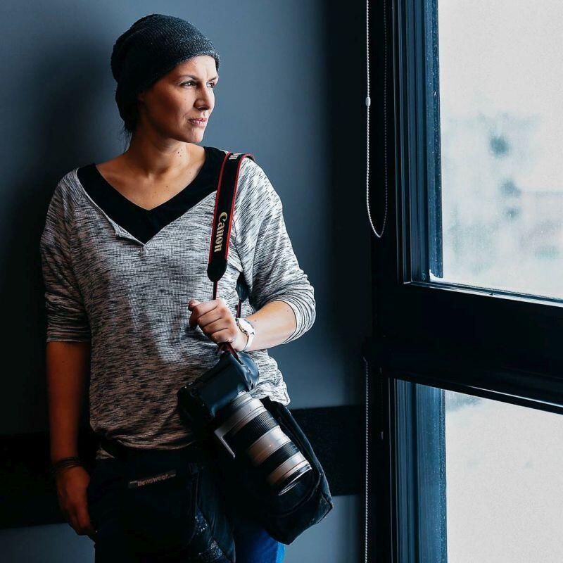 zdjęcie młodej kobiety w czapce z aparatem na tle okna