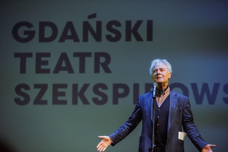 Po prawej, przy mikrofonie, stoi postać mężczyzny około lat sześćdziesięciu, z artystyczną burzą siwych włosów. Ubrany jest w niebieską marynarkę, pod szyją ma apaszkę. Na ekranie, który stoi za nim, wyświetlony jest wielki napis: Gdański Teatr Szekspirowski